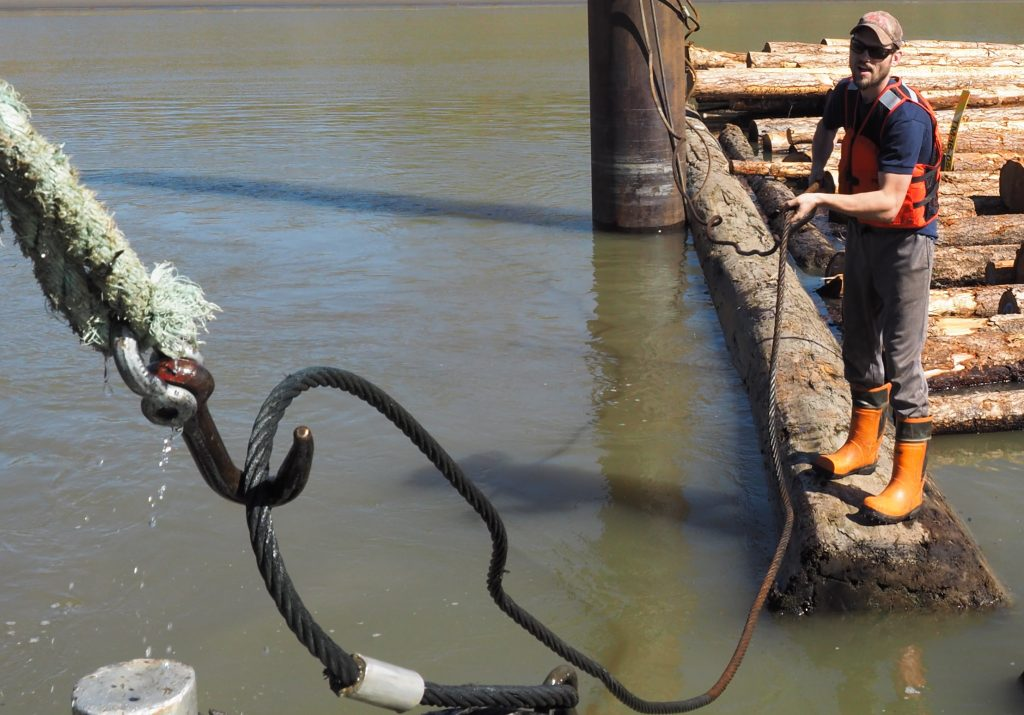 The captain and deckhand work together to fish a sunken cable from the water.