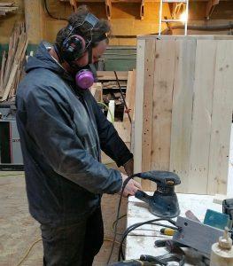 Piche working on a wooden shelf