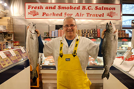 Granville Island Longliner Seafoods Ltd. business owner Scott Moorehead holds up Pacific Chinook salmon for sale.