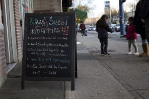 View of a sandwich board on a sidewalk with colourful chalk writing on it, advertising weekly specials for bubble-tea flavours.