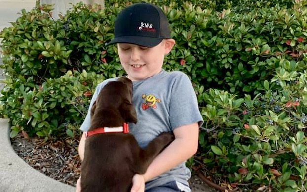 A young boy with a black baseball cap plays with a puppy