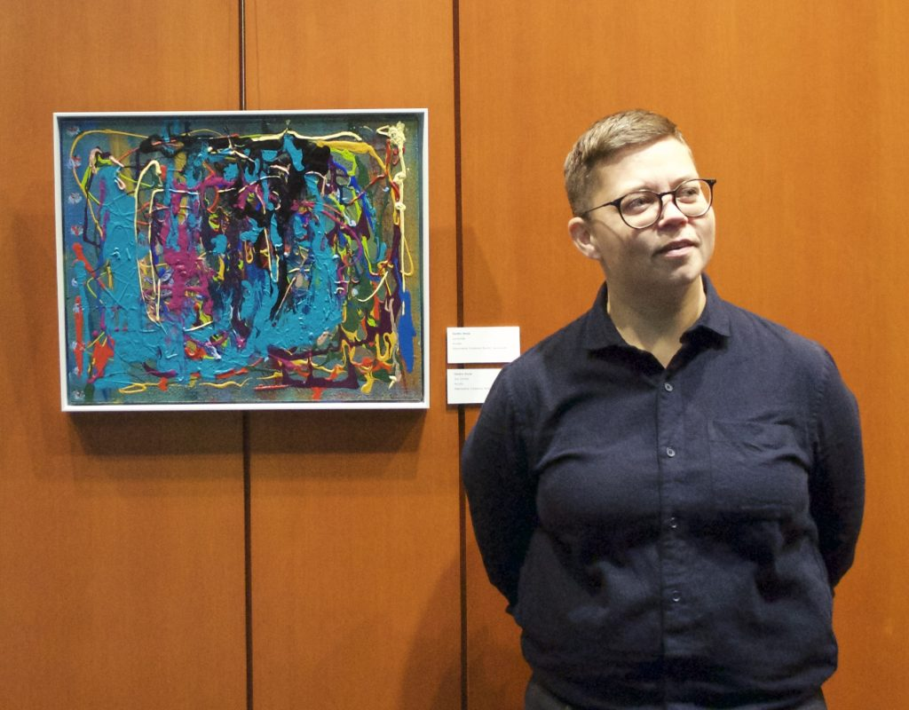 Amy Nugent, executive director of Inclusion BC Foundation stands beside a painting by artist Deidre Snow, who is also a member of the BridgeArt studio in Langley.